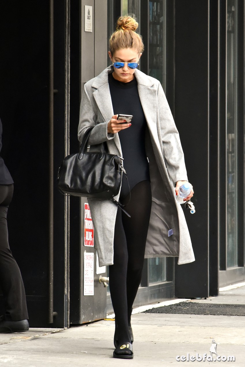 "Gigi Hadid heads to the gym in black tights and ""GI"" initial sandals."